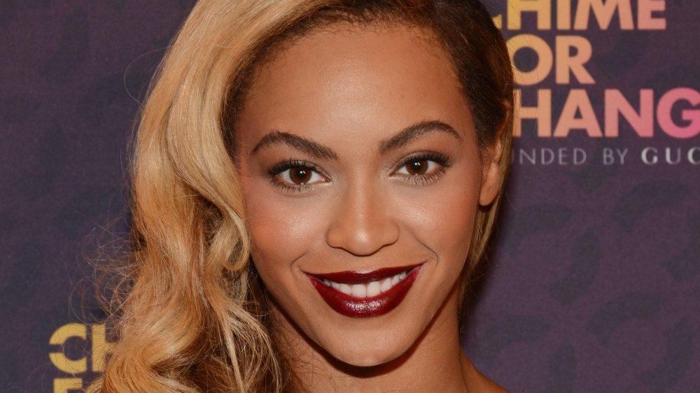 Beyoncé con el pelo largo rubio y lápiz labial rojo oscuro, sonriendo