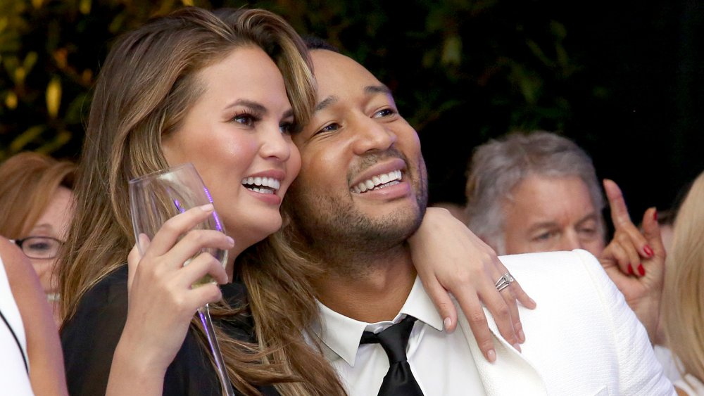 Chrissy Teigen sosteniendo una copa de champán, abrazando a John Legend