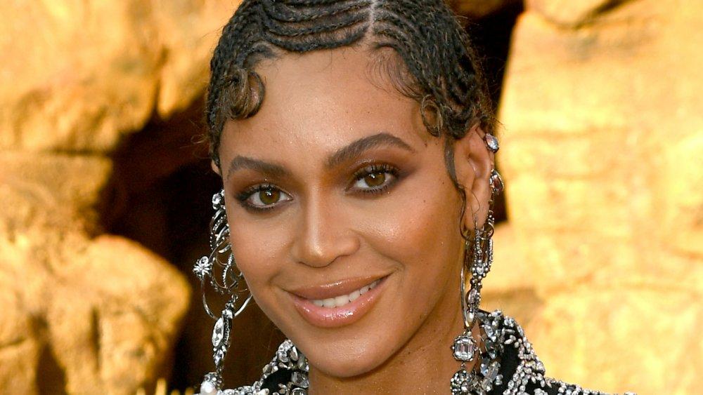 Beyoncé con un traje negro brillante, sonriendo en el estreno de El Rey León
