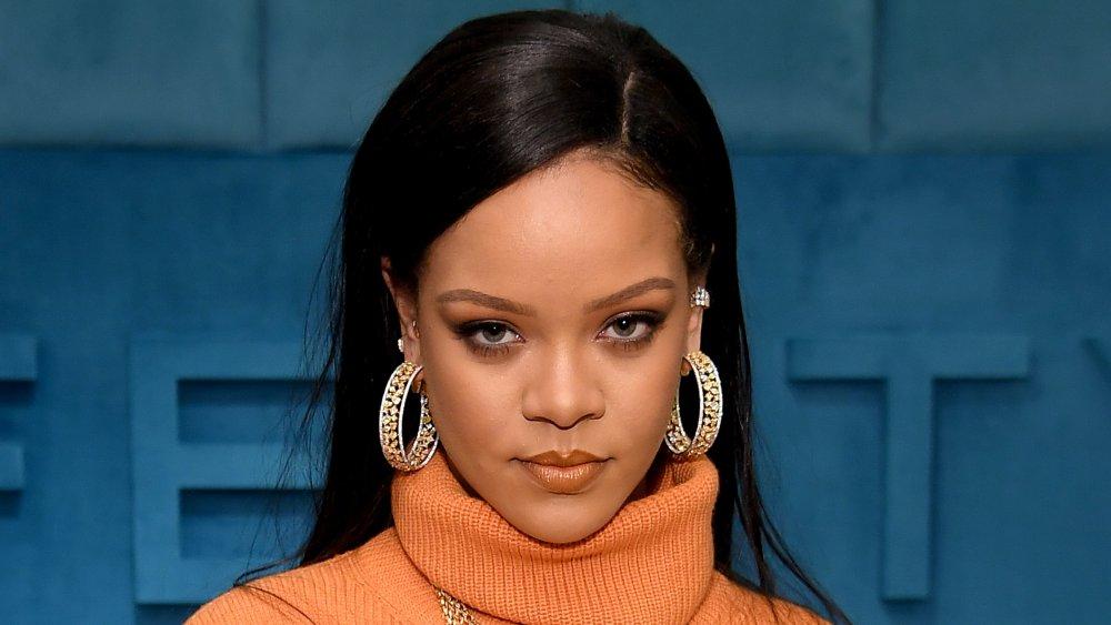 Rihanna con un vestido de cuello de tortuga naranja, posando con una expresión seria