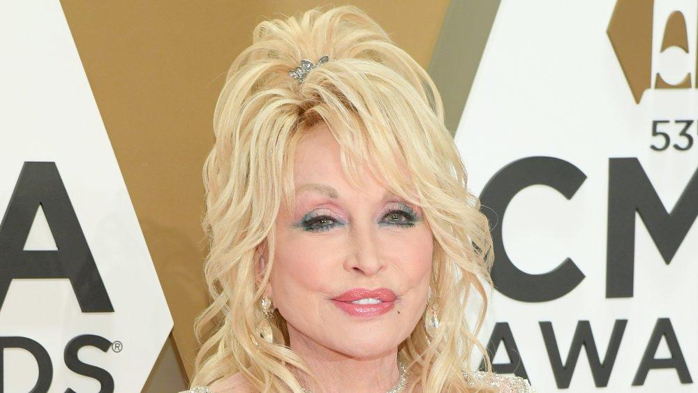 Dolly Parton con un vestido blanco brillante, posando en los Premios CMA