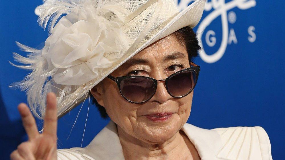 Yoko Ono con un blazer blanco, sombrero y gafas de sol, sonriendo y dando el signo de paz