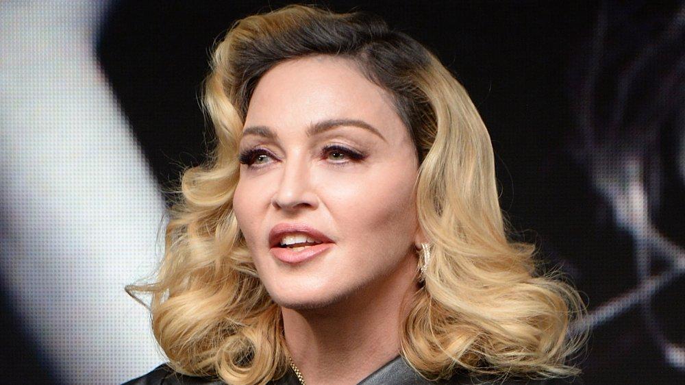 Madonna con un traje de cuero negro, hablando mientras mira hacia un lado