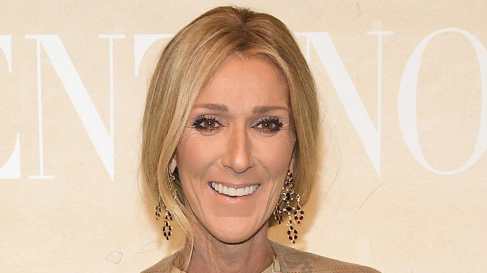 Céline Dion con un traje beige y pendientes colgantes, sonriendo grande