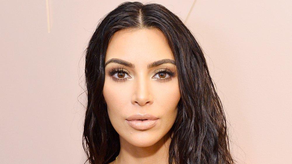 Kim Kardashian con un vestido blanco y un look de pelo mojado, posando con una expresión sorprendida