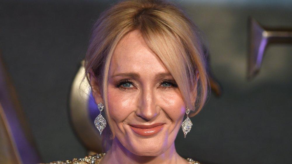 J.K. Rowling con un vestido brillante de oro, sonriendo con el pelo recogido
