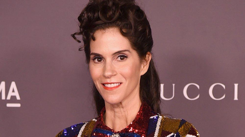 Jami Gertz en un vestido rojo, azul y dorado brillante, sonriendo y mirando hacia un lado
