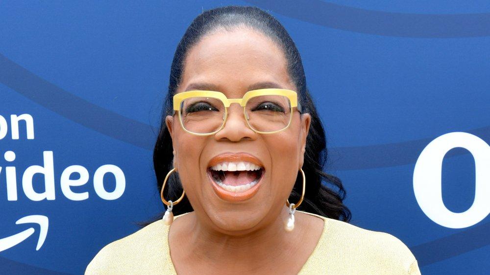 Oprah Winfrey con un vestido y gafas amarillas, riendo mientras mira directamente a la cámara