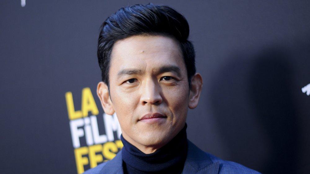John Cho en un blazer azul y cuello de tortuga, posando con una expresión seria