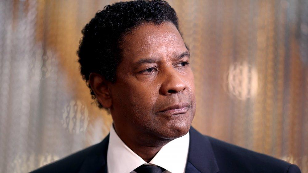 Denzel Washington en un clásico traje negro y combo de corbata, que se ve serio mientras mira hacia un lado