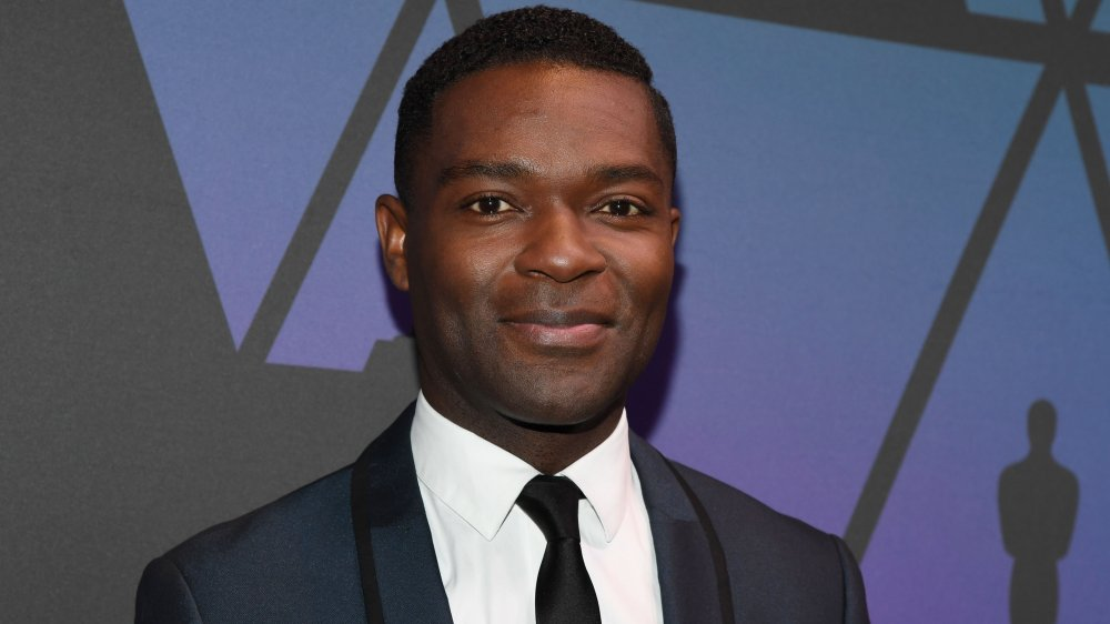 David Oyelowo en un traje azul oscuro, forrado en negro, posando con una pequeña sonrisa en los Oscar