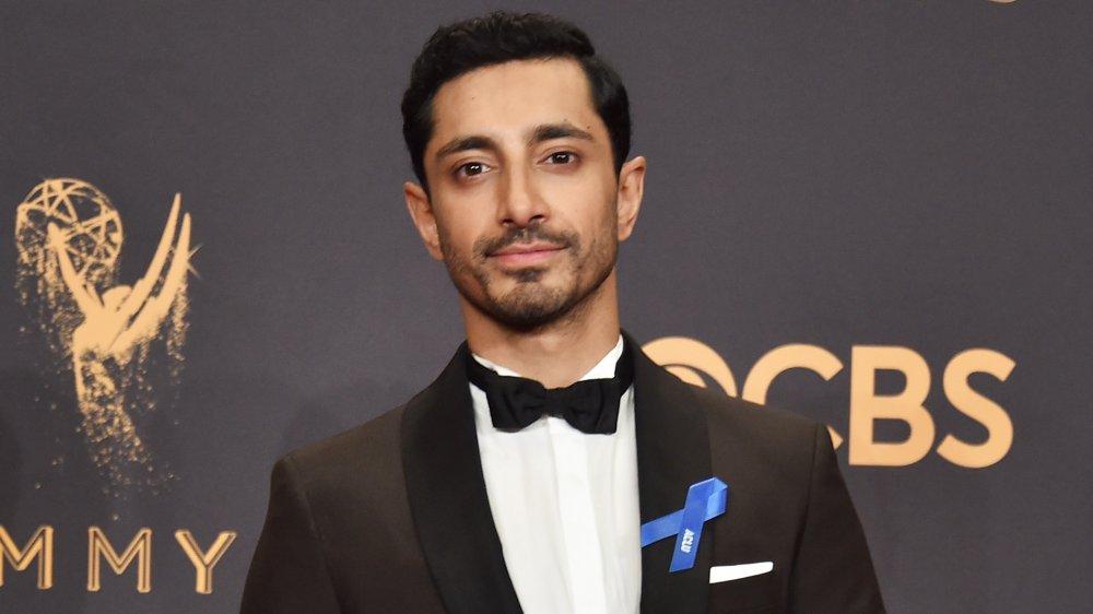 Riz Ahmed con traje negro y pajarita, posando con su Emmy