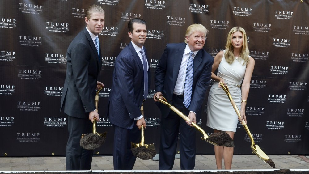 Eric Trump, Donald Trump Jr., Donald Trump e Ivanka Trump sostienen palas de oro con tierra