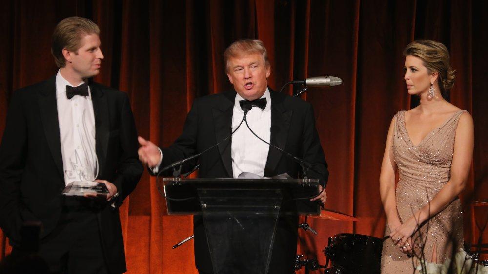 Eric Trump, Donald Trump e Ivanka Trump de pie en un podio