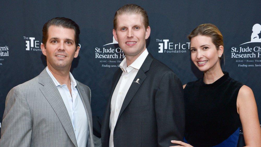 Donald Trump Jr., Eric Trump e Ivanka Trump posando frente a la pared