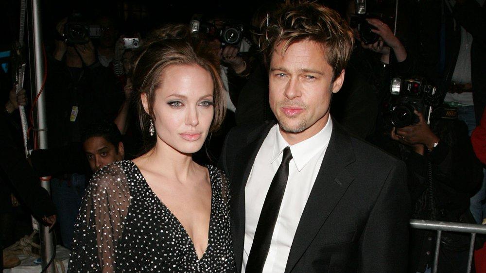 Angelina Jolie y Brad Pitt, posando junto con expresiones serias, rodeados de fotógrafos