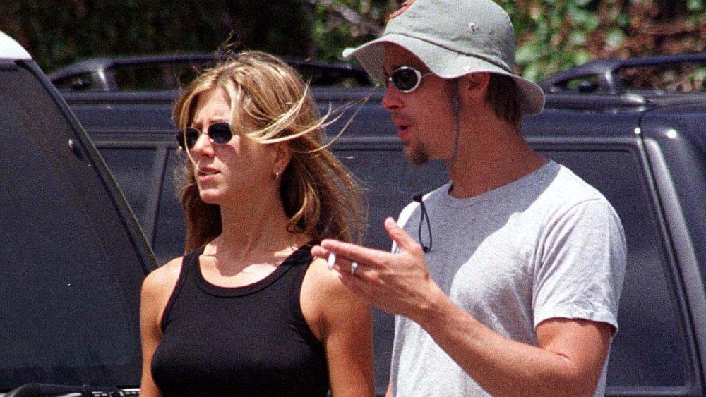 Jennifer Aniston y Brad Pitt, ambos con gafas de sol, hablando mientras caminan en un estacionamiento