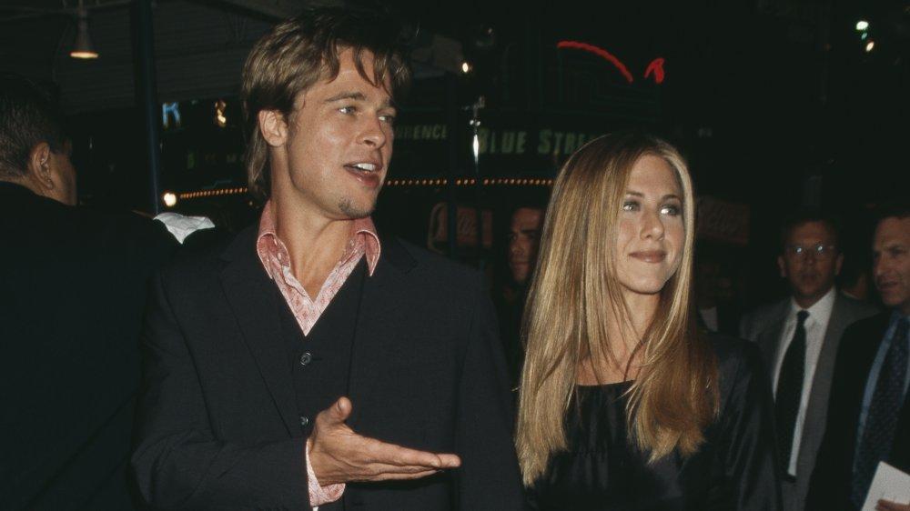 Brad Pitt y Jennifer Aniston, ambos vestidos de negro, cogidos de la mano y caminando un evento de alfombra roja