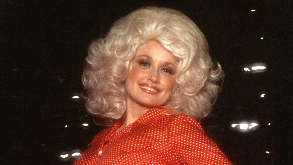 Dolly Parton con el pelo rubio grande y camisa roja botón arriba