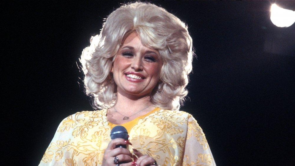Young Dolly Parton sonriendo en el escenario