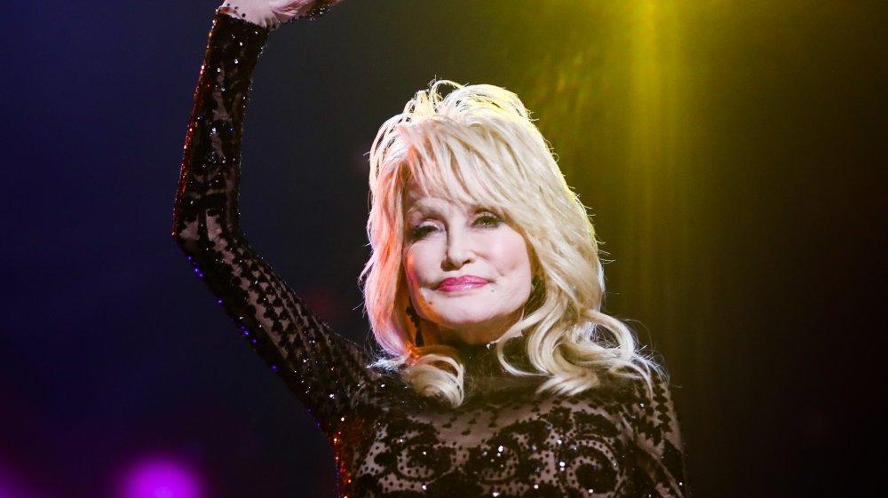 Dolly Parton en el escenario con un vestido negro de lentejuelas
