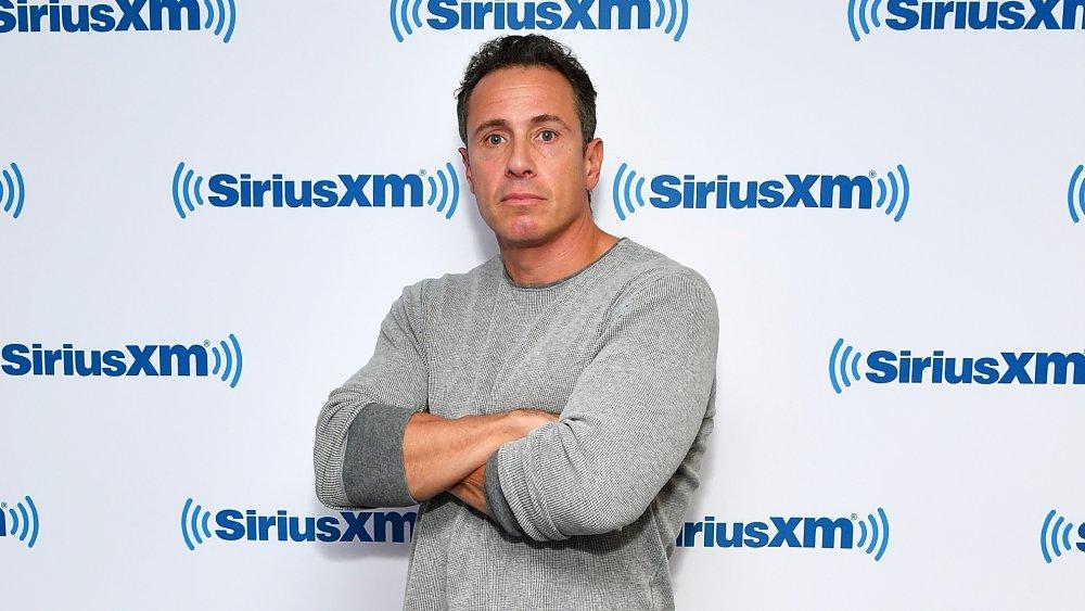 Chris Cuomo, con los brazos cruzados, frente a la pared de SiriusXM