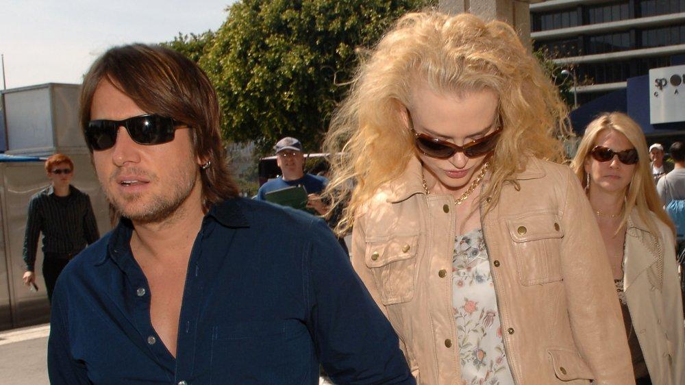 Keith Urban mirando en serio, Nicole Kidman mirando hacia abajo, ambos usando gafas de sol
