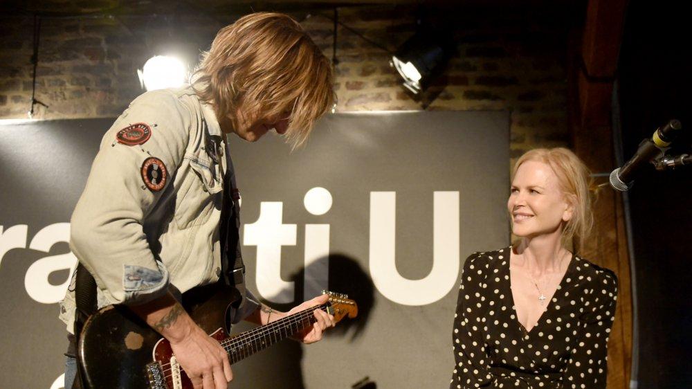 Nicole Kidman sonriendo mientras ve a Keith Urban tocar la guitarra