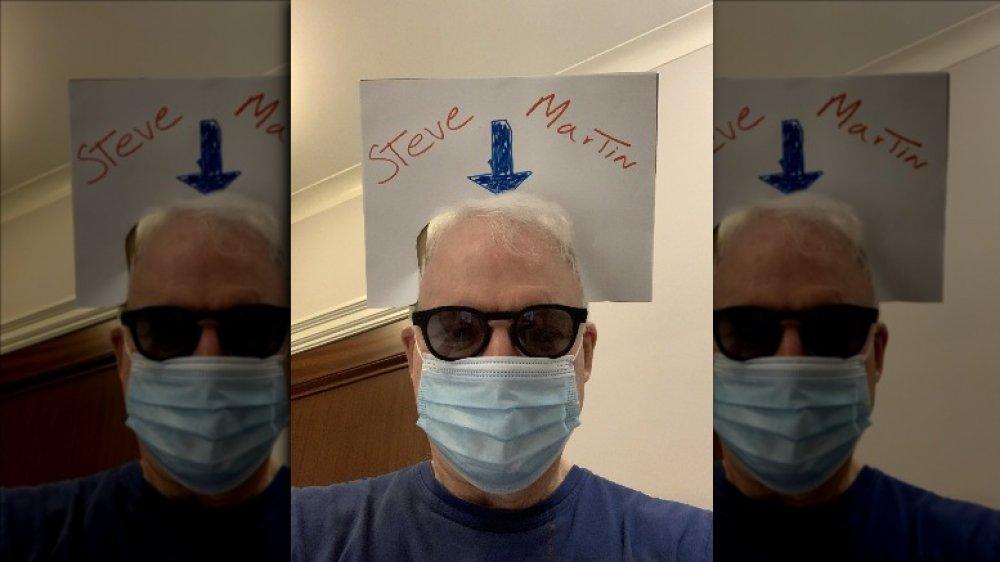 Steve Martin en su máscara con un cartel en la cabeza