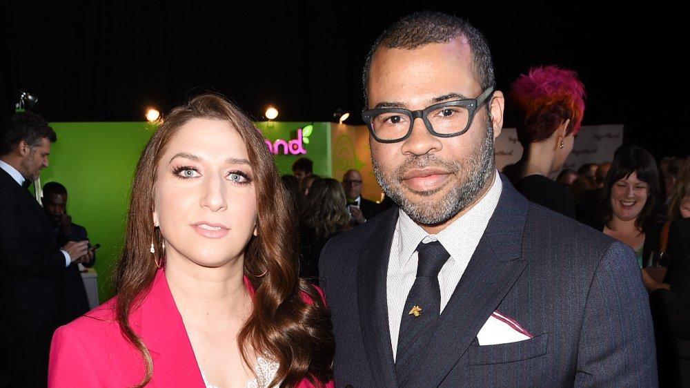 Chelsea Peretti en un blazer rosa, Jordan Peele con un traje y gafas de rayas de alfiler negro y azul
