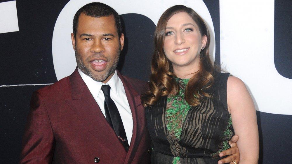 Jordan Peele en traje granate, Chelsea Peretti con un vestido verde y negro