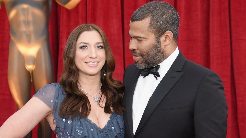 Chelsea Peretti sonriendo con un vestido azul, Jordan Peele en un traje negro mirando a su