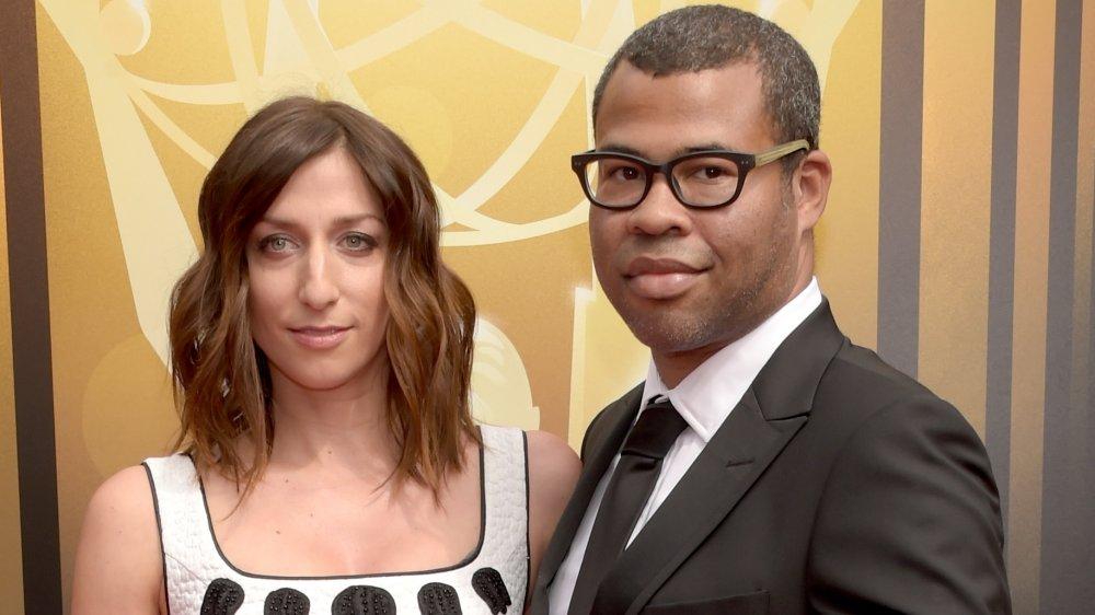 Chelsea Peretti con un vestido blanco y negro, Jordan Peele con traje y gafas negras