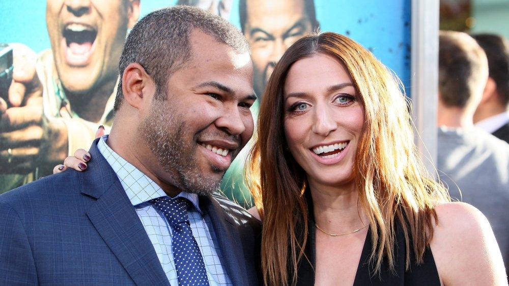 Jordan Peele en un traje azul, Chelsea Peretti con un vestido negro, ambos sonriendo grande