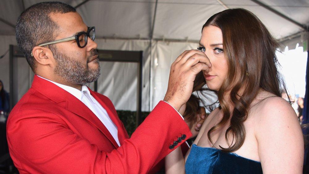 Jordan Peele con traje rojo, arreglando el cabello de Chelsea Peretti