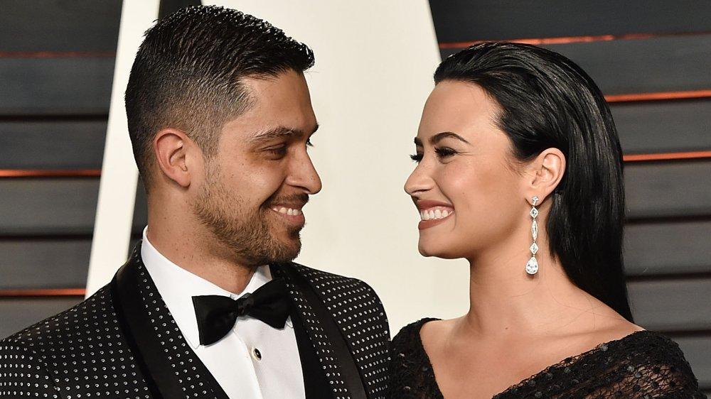 Wilmer Valderrama y Demi Lovato sonriendo el uno al otro