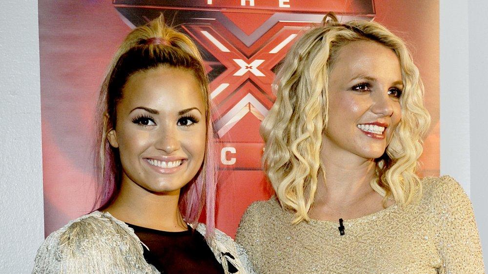 Demi Lovato y Britney Spears posando y sonriendo