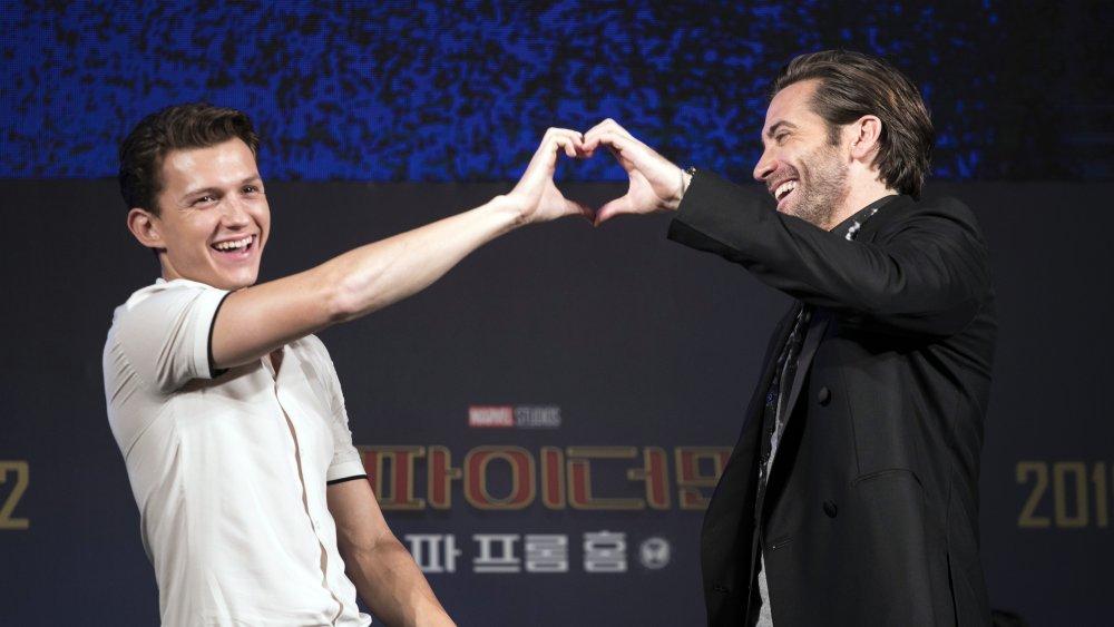 Tom Holland y Jake Gyllenhaal se ríen mientras forman un corazón con las manos en un evento de prensa de Spider-Man: Far From Home