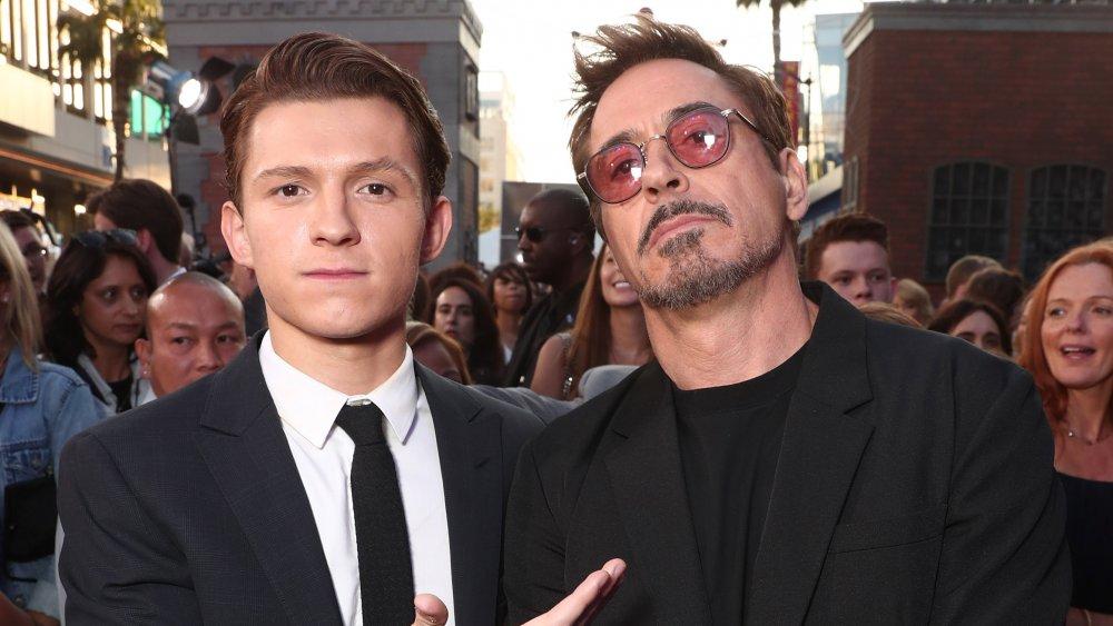 Tom Holland y Robert Downey Jr., posando en un estreno de película con expresiones serias