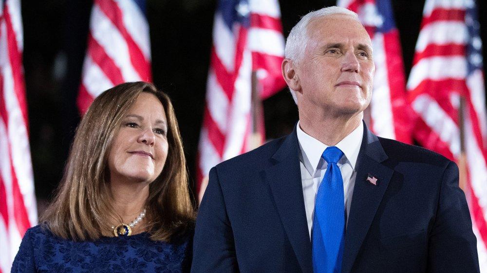 Karen y Mike Pence miran y sonríen frente a las banderas de EE.UU.