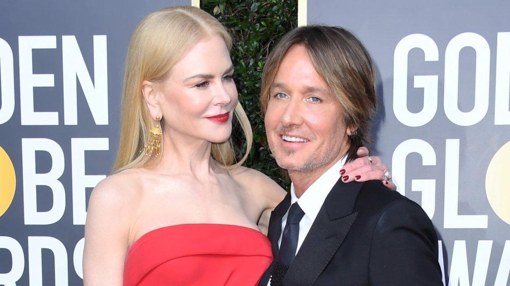 Nicole Kidman con un vestido rojo con el brazo alrededor del hombro de Keith Urban