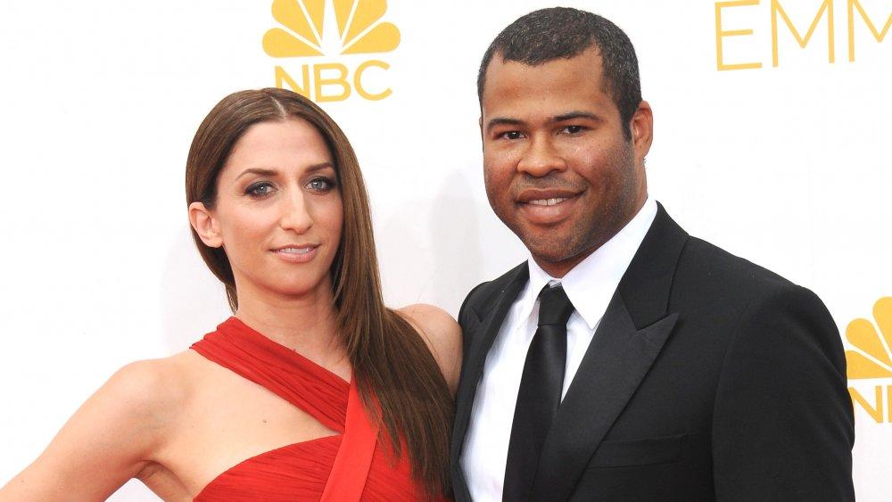 Chelsea Peretti con un vestido rojo, Jordan Peele con un traje negro, ambos sonriendo a los Emmy