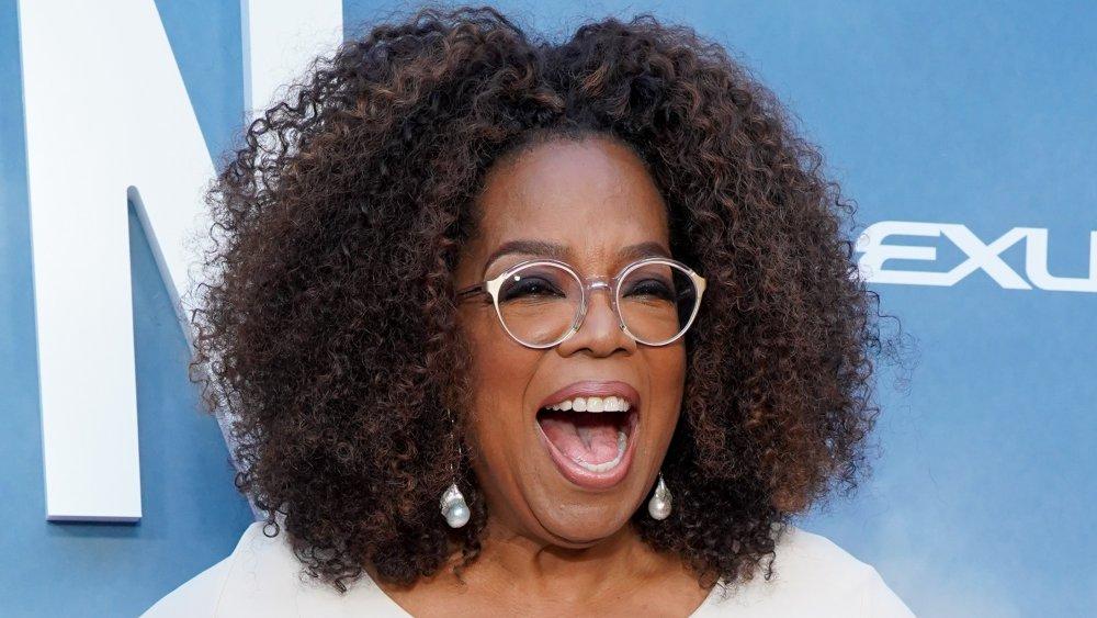 Oprah Winfrey con un traje blanco, riendo en la alfombra roja
