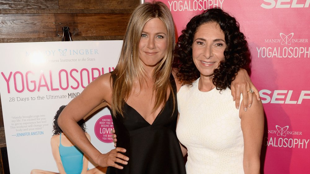 Jennifer Aniston y la inventora de Yogalosophy Mandy Ingber, sonriendo y posando del brazo