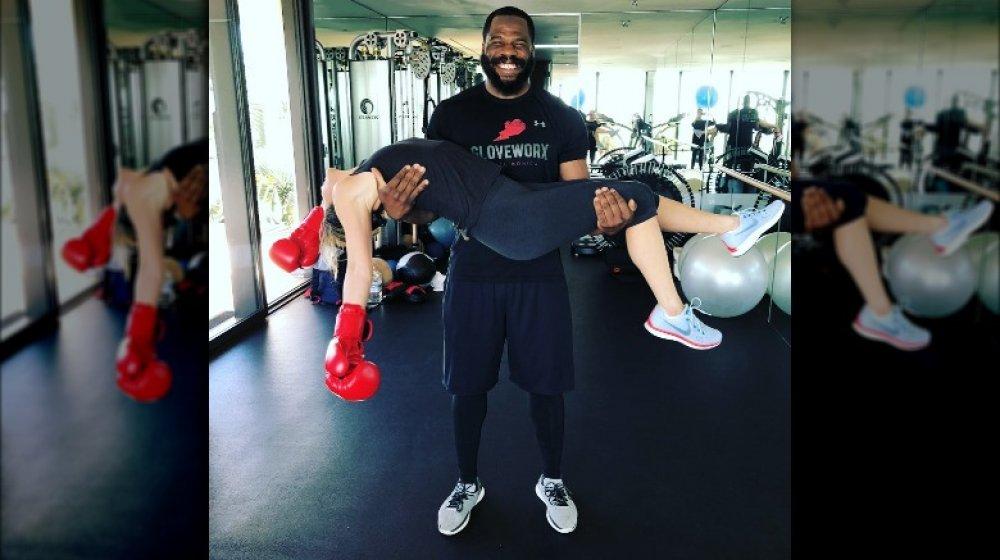 Entrenador Leyon Azubuike sosteniendo a Jennifer Aniston después de una sesión de boxeo