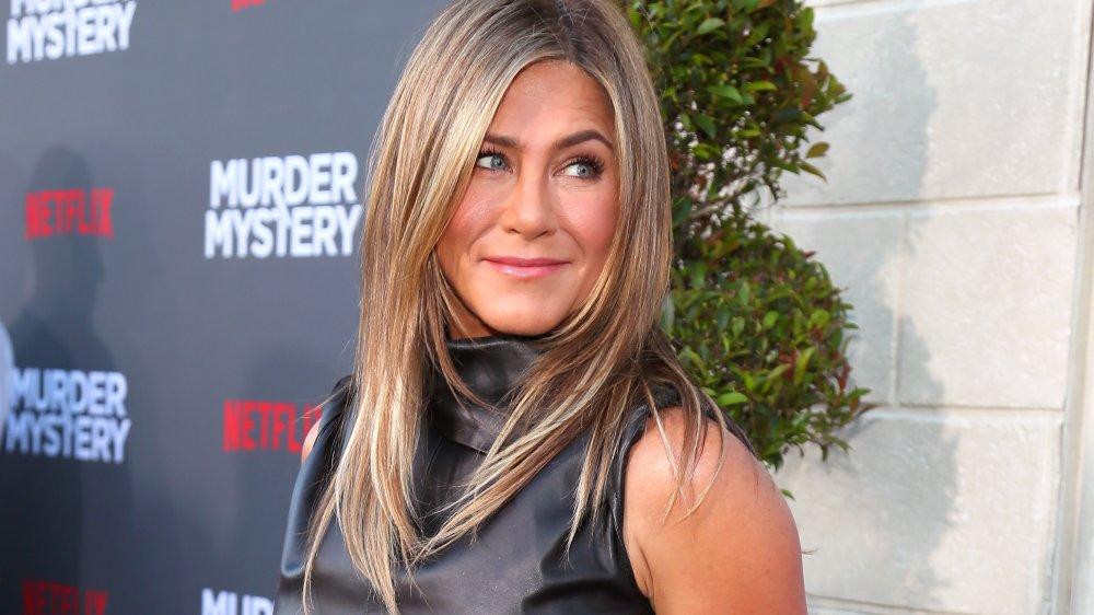 Jennifer Aniston sonriendo mientras mira por encima del hombro en el estreno de Murder Mystery