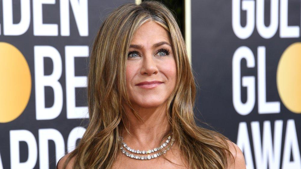 Jennifer Aniston sonriendo y mirando hacia los Globos de Oro 2020
