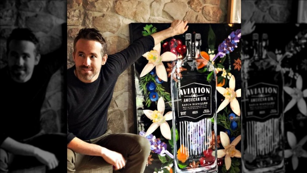 Ryan Reynolds posando con una pintura de una botella de ginebra Aviation