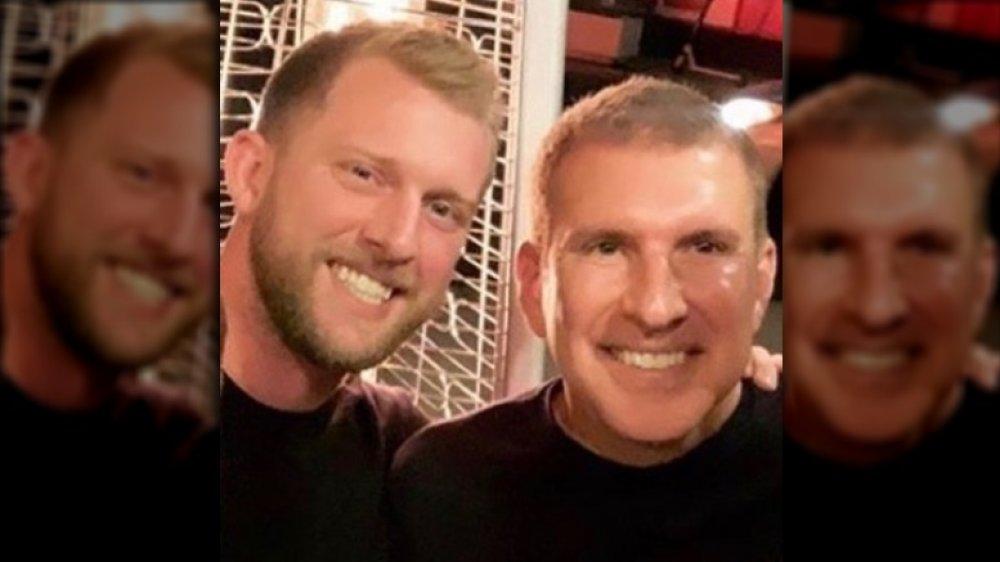 Kyle Chrisley y Todd Chrisley sonriendo y abrazándose