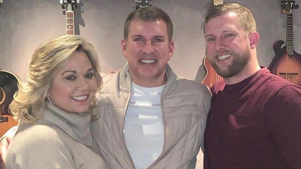 Julie Chrisley, Todd Chrisley y Kyle Chrisley abrazándose y sonriendo